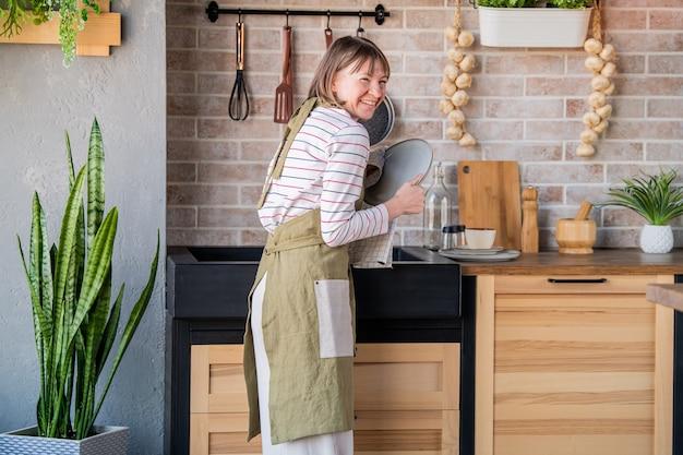 Śmiejąca się kobieta w lnianym fartuchu stojąca w kuchni przy zlewie wycierająca talerz lnianym ręcznikiem