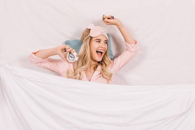 Śmiejąca się kobieta w masce do spania, leżąc w łóżku