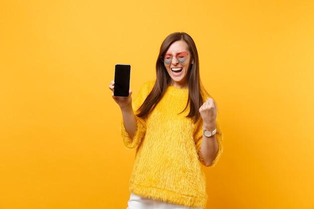 Śmiejąca się kobieta w okularach serca zaciskając pięść jak zwycięzca trzymając telefon komórkowy z pustym czarnym pustym ekranem na białym tle na jasnym żółtym tle. ludzie szczere emocje styl życia. powierzchnia reklamowa.