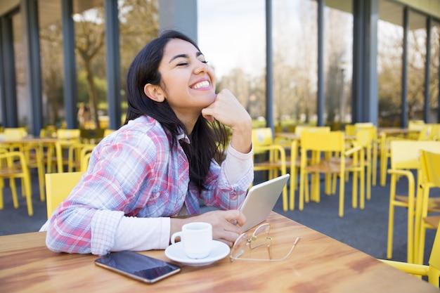 Śmiejąca się kobieta za pomocą gadżetów i picia kawy w kawiarni
