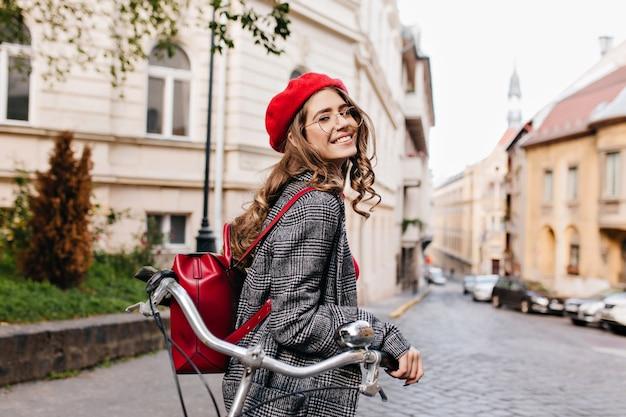 Śmiejąca się kręcona ciemnowłosa dziewczyna oglądająca się za siebie, stojąca rano na starej ulicy