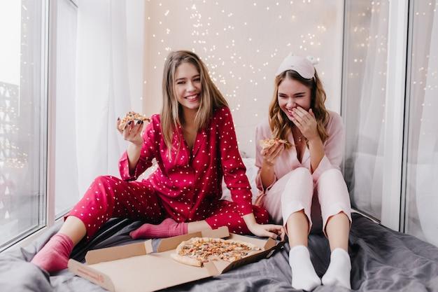Śmiejąca się kręcona dziewczyna w różowych skarpetkach siedzi na czarnym prześcieradle z kawałkiem pizzy. kryty portret koleżanki, jedzenie fast food w łóżku i żartuje.