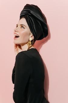 Śmiejąca się ładna kobieta pozuje w turbanie i złote kolczyki