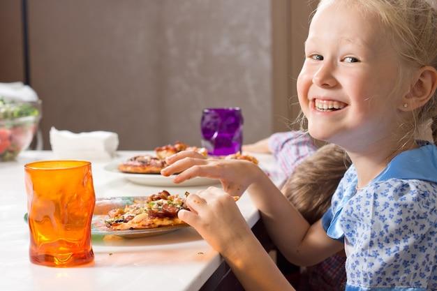 Śmiejąca się mała dziewczynka je domową pizzę