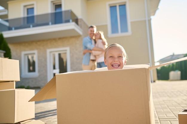 Śmiejąca się mała dziewczynka wyglądająca z dużego pudełka
