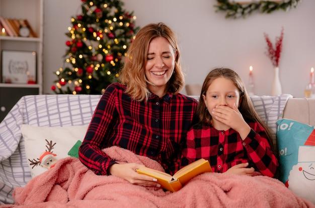 Śmiejąca się matka i córka, czytanie książki przykrytej kocem, siedząc na kanapie i ciesząc się boże narodzenie w domu