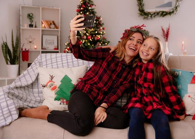 Śmiejąca się matka z wieńcem ostrokrzewu i córka patrzą na telefon, biorąc selfie, siedząc na kanapie i ciesząc się świątecznym w domu