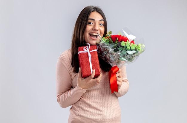 Śmiejąca się młoda dziewczyna na walentynki trzymająca pudełko z bukietem na białym tle