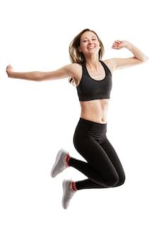 Śmiejąca się młoda kobieta w odzieży sportowej skacze emocjonalnie.