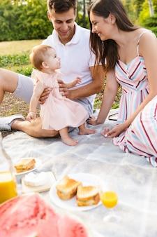 Śmiejąca się młoda rodzina z małą córeczką