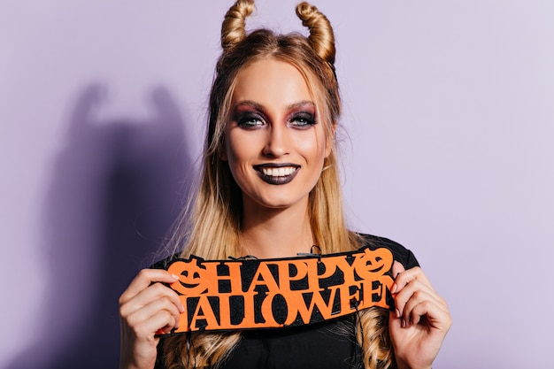 Śmiejąca się modelka z ciemnym makijażem halloween, pozowanie na fioletowej ścianie. kryty zdjęcie ładnej blondynki.
