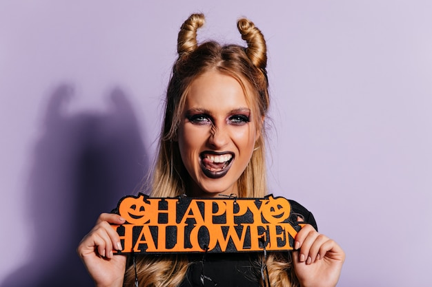 Śmiejąca się niebieskooka dziewczyna korzystających z karnawału. pozytywna młoda czarownica mrożąca krew w żyłach w halloween.