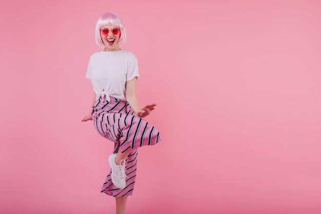 Śmiejąca się oszałamiająca kobieta w okularach przeciwsłonecznych tańcząca na różowej ścianie. wesoła europejska modelka w czarujący peruke zabawy