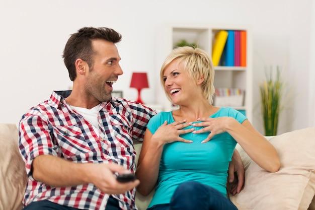 Śmiejąca się para spędzająca czas w domu przy zabawnym filmie