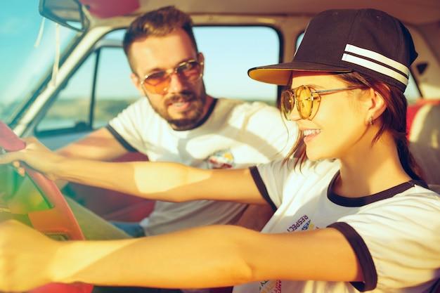 Śmiejąca się romantyczna para siedząca w samochodzie podczas wycieczki samochodowej
