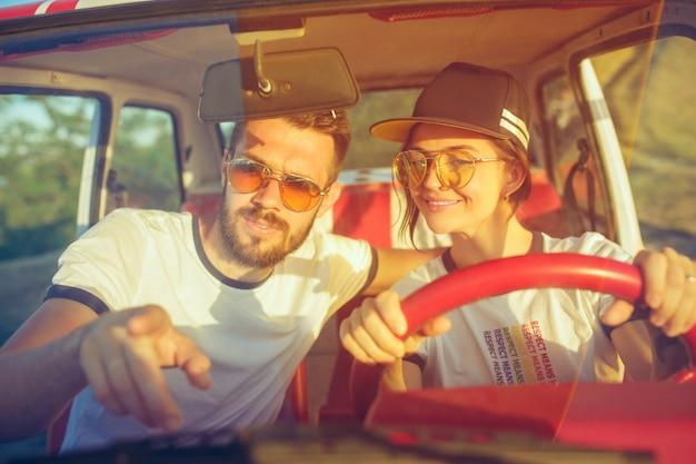 Śmiejąca się romantyczna para siedzi w samochodzie podczas podróży.