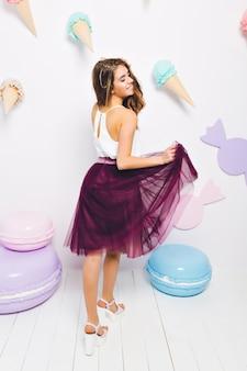 Śmiejąca się rozmarzona dziewczyna w białym podkoszulku bawiąca się bujną spódnicą, stojąca obok kolorowych zabawkowych makaroników. bardzo elegancka młoda kobieta w romantyczny strój taniec na weselu.