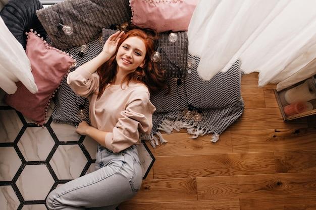 Śmiejąca się rudowłosa dziewczyna w dżinsach siedzi obok poduszek. kryty zdjęcie uśmiechniętej rudej pani leżącej na podłodze.