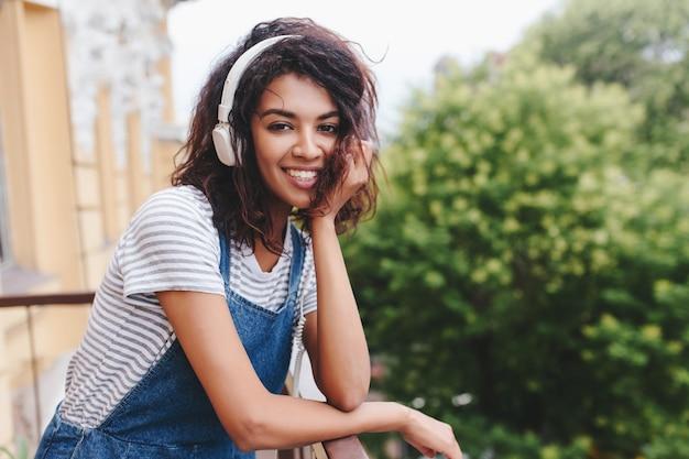 Śmiejąca się śliczna dziewczyna z modną kręconą fryzurą siedzi na zewnątrz i pozuje na drzewie