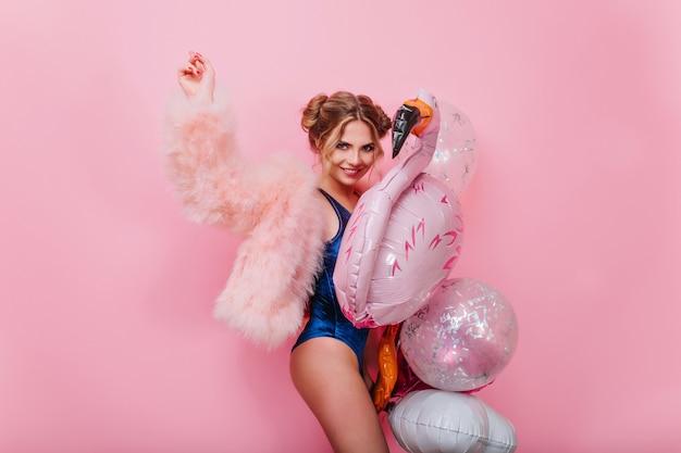 Śmiejąca się stylowa dziewczyna w puszystej różowej kurtce tańczy z balonami imprezy, czekając na przyjaciół. urocza młoda kobieta w niebieskim body, zabawy z zabawkami flamingo, gotowa na przyjęcie przy basenie.