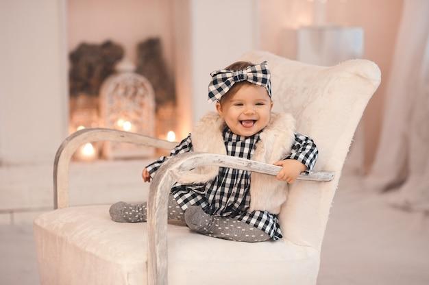 Śmiejąca się stylowa dziewczynka siedzi na krześle nad bożonarodzeniowymi lampkami