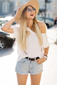 Śmiejąca się szczęśliwa dziewczyna ubrana w stylowy kapelusz i dżinsowe szorty śmieje się na ulicy. letnie spacery w słońcu z ogromnymi emocjami.
