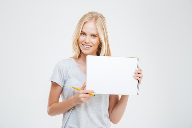 Śmiejąca się wesoła ładna dziewczyna pokazująca pusty zeszyt na białym tle na białej ścianie