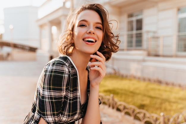 Śmiejąca się wspaniała kobieta z bladą skórą, pozowanie na ulicy rozmycia. marzycielska młoda dama w dobrym nastroju spędzająca czas na świeżym powietrzu.