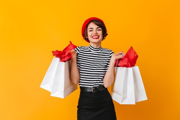 Śmiejąca się wyrafinowana kobieta w pasiastej koszulce trzymającej torby sklepowe