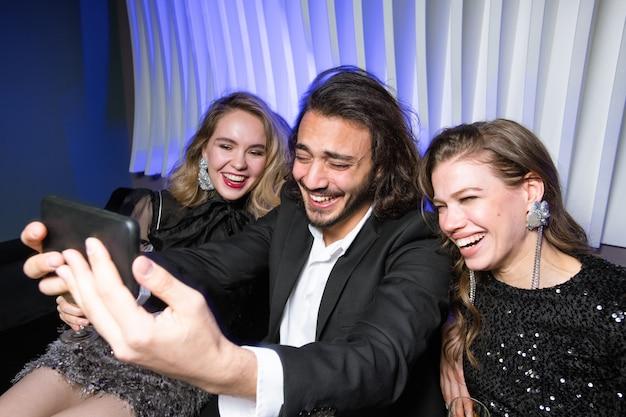 Śmiejące się czarujące dziewczyny i elegancki mężczyzna ze smartfonem robiącym selfie, ciesząc się imprezą w nocnym klubie