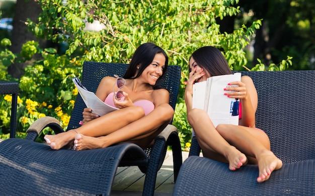 Śmiejące się dwie młode dziewczyny czytające magazyn na leżaku na świeżym powietrzu
