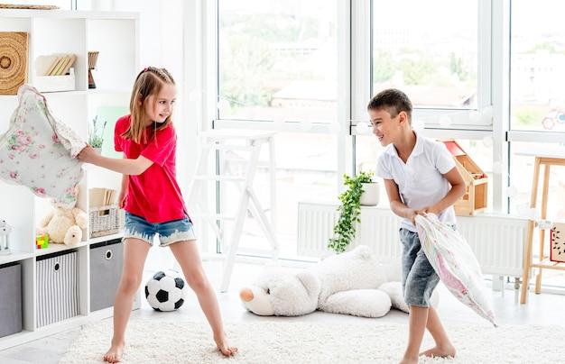 Śmiejące się dzieci bawiące się podczas walki na poduszki w domu