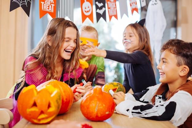Śmiejące się dzieci. czwórka dzieci w kostiumach na halloween śmiejących się głośno podczas imprezy w przestronnym, jasnym pokoju