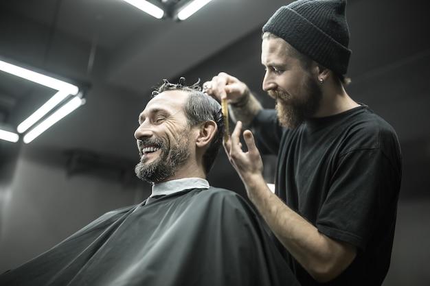 Śmiejący się brodaty mężczyzna z zamkniętymi oczami w czarnej tnącej pelerynie w zakładzie fryzjerskim