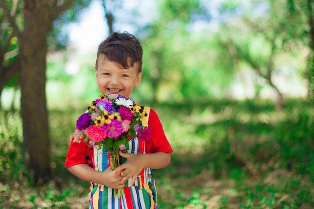 Śmiejący się chłopiec z bukietem dzikich kwiatów w dłoniach na tle przyrody dzień matki