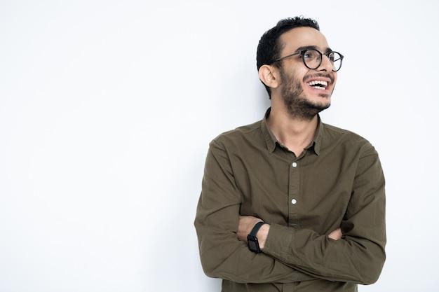 Śmiejący się facet w okularach i odzieży codziennej krzyżujący ramiona na klatce piersiowej, stojąc w izolacji z copyspace po lewej stronie
