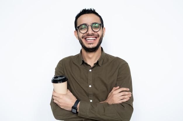 Śmiejący się facet ze szklanką kawy, krzyżując ramiona na klatce piersiowej, stojąc w izolacji na białym tle