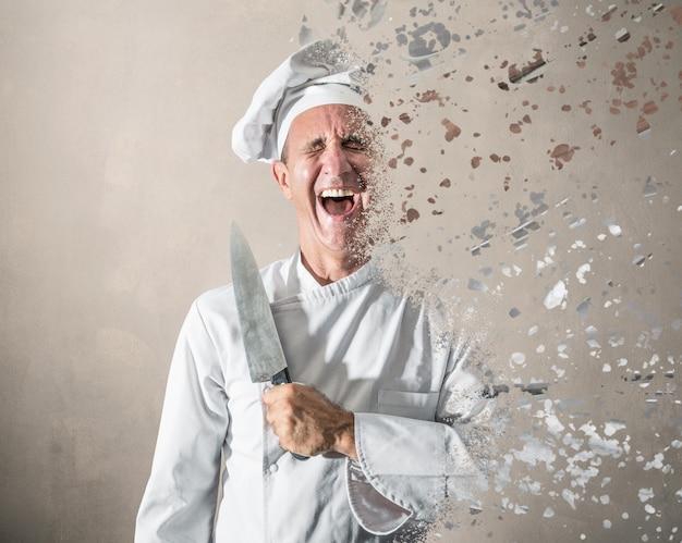 Śmiejący się kucharz z nożem w dłoni rozpuszcza się