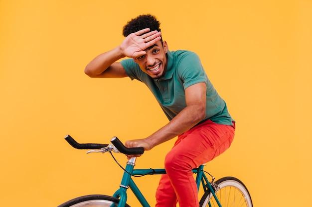 Śmiejący się mężczyzna siedzi na rowerze z kręconymi fryzurami. afrykański facet w kolorowe stroje, jazda na rowerze.