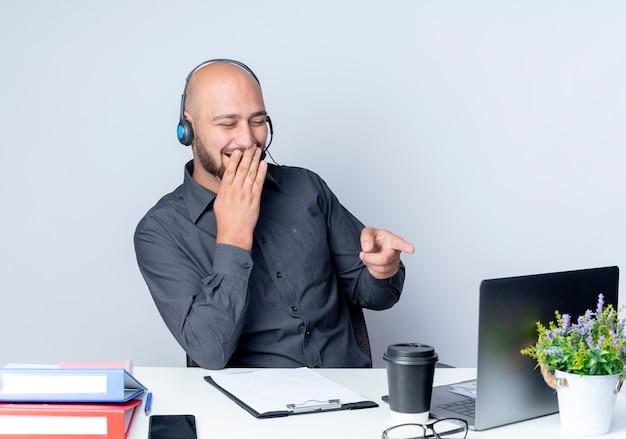 Śmiejący się młody łysy mężczyzna z call center w zestawie słuchawkowym siedzi przy biurku z narzędziami roboczymi patrząc i wskazując na laptopa z ręką na ustach na białym tle