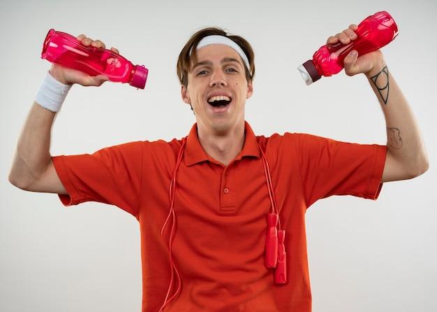Śmiejący się młody sportowy facet ubrany w opaskę z opaską z skakanką na ramieniu, podlewanie się butelką wody na białym tle