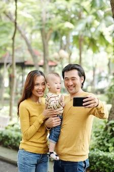 Śmiejący się młodzi rodzice i ich synek śmiejący się podczas wspólnego robienia selfie w parku