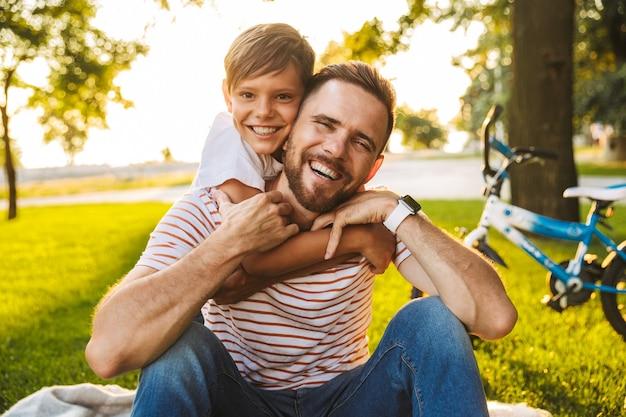 Śmiejący się ojciec i jego syn bawią się razem