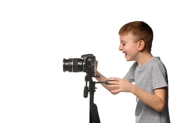 Śmiejący się uczeń kręci wideo aparatem dslr