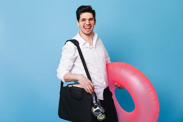Śmieje się młody brunet w okularach. facet w garniturze trzyma różowy gumowy pierścień i maskę do nurkowania.