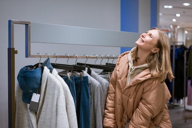 Śmieje się szczęśliwa śliczna kobieta w ciepłej kurtce w sklepie odzieżowym
