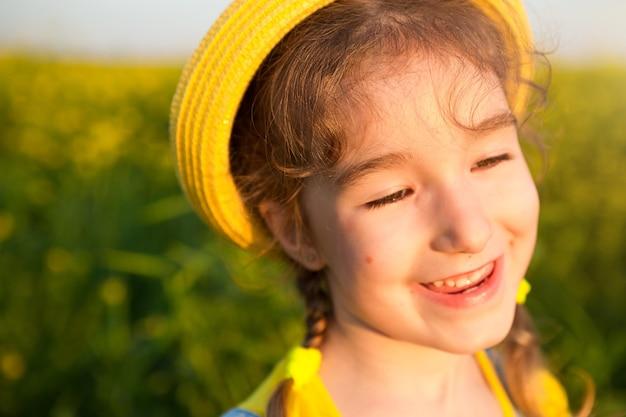 Śmieje się wesoła dziewczyna w żółtym kapeluszu w letnim polu. beztroska, radość, słoneczna pogoda, wakacje. środek na komary i owady. styl życia, miła twarz, portret z bliska