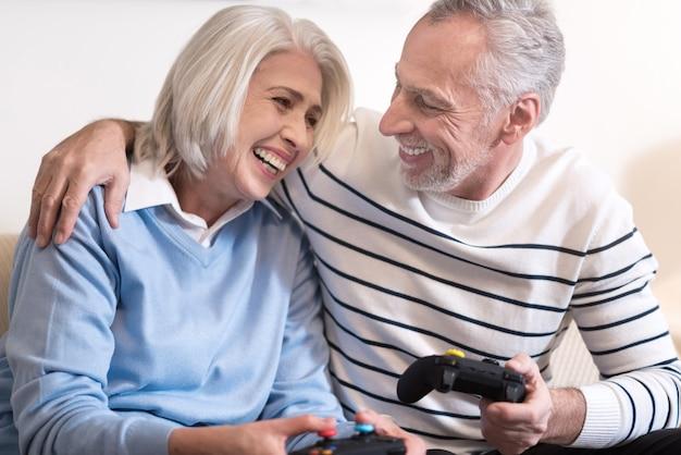 Śmiejemy się razem. wesoła uśmiechnięta para w wieku trzymając konsole do gier, siedząc na kanapie i śmiejąc się razem