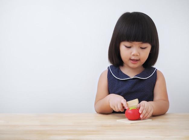 Śmieszna azjatykcia dzieciak dziewczyna bawić się z drewnianą kucharstwo zabawką, mały szefa kuchni narządzania jedzenie na kuchennym kontuarze.