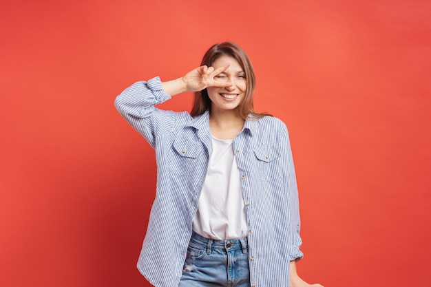 Śmieszna, beztroska dziewczyna ma zabawę odizolowywającą na czerwonej ścianie